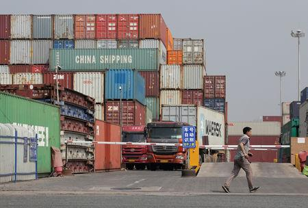 FILE PHOTO: A man walks next to containers in a logistics center near Tianjin Port, in northern China, May 16, 2019. REUTERS/Jason Lee/File Photo