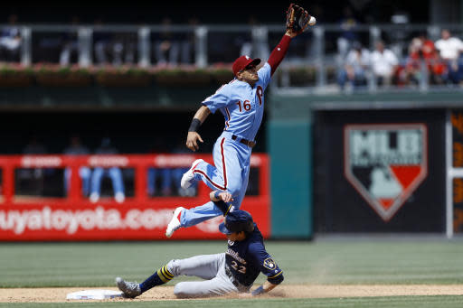 Milwaukee Brewers' Christian Yelich, bottom, steals second base as Philadelphia Phillies second baseman Cesar Hernandez leaps for the overthrow during the sixth inning of a baseball game, Thursday, May 16, 2019, in Philadelphia. Yelich advanced to third on the overthrow. (AP Photo/Matt Slocum)