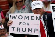 Republican U.S. presidential nominee Donald Trump holds up signs at the end of a campaign rally in Lakeland, Florida, U.S., October 12, 2016. REUTERS/Mike Segar/File Photo