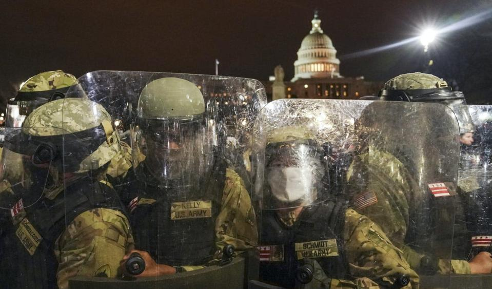 """<span class=""""caption"""">DC National Guard stand outside the Capitol on Jan. 6, 2021, after Trump supporters stormed the building in an attempt to overturn the U.S. presidential election.</span> <span class=""""attribution""""><span class=""""source"""">(AP Photo/John Minchillo)</span></span>"""