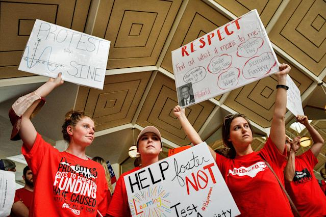 <p>Teachers and supporters hold signs during a 'March For Students And Rally For Respect' protest at the North Carolina State Assembly, on the first day of the state's legislative session, in Raleigh, N.C., on Wednesday, May 16, 2018. At least 29 North Carolina public school districts serving 865,000 students will close their doors as teachers walk out in the fifth large-scale demonstration in less than three months in states with Republican-led legislatures, most of them organized on the internet in places where unions are weak. (Photo: Charles Mostoller/Bloomberg via Getty Images) </p>