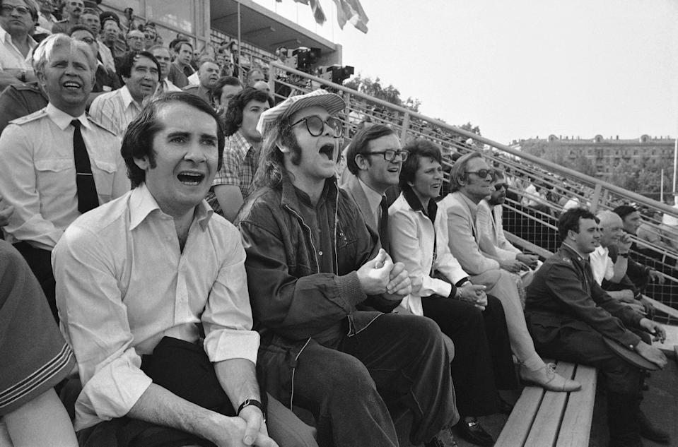 British rock star Elton John, foreground, and his manager John Reid, left, attend a soccer match in Moscow between the Central Army Club and Dynamo Minsk, May 26, 1979. (AP Photo/Boris Yurchenko)