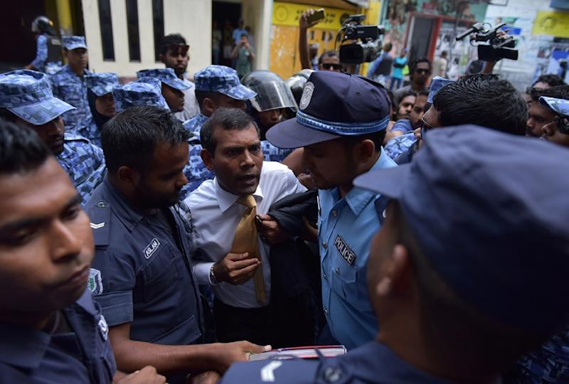 Maldives police try to move former president Mohamed Nasheed (C) during a scuffle as he arrives at a courthouse in Male on February 23, 2015 (AFP Photo/Adam Sireii)