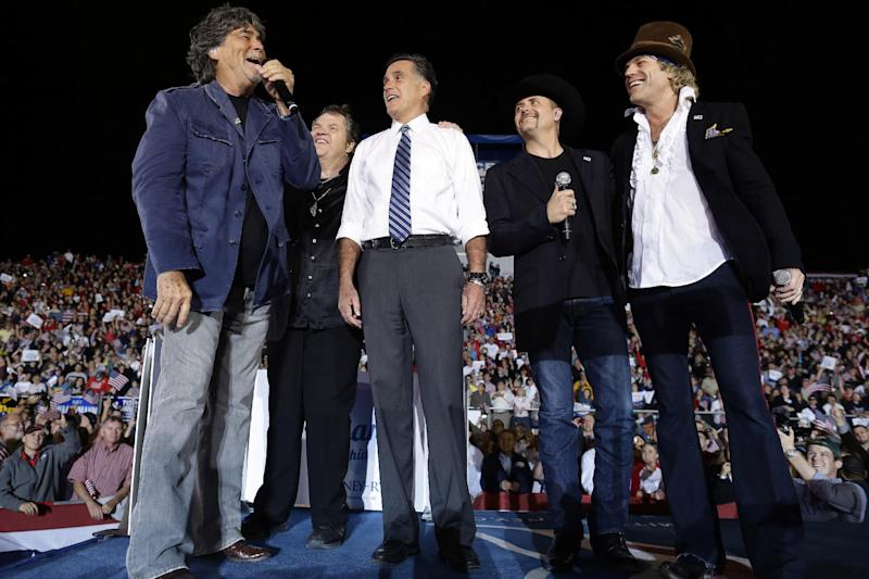 """Republican presidential candidate and former Massachusetts Gov. Mitt Romney sings """"God Bless America"""" as he campaigns at the football stadium at Defiance High School in Defiance, Ohio, Thursday, Oct. 25, 2012, with from left to right, Randy Owen, Meat Loaf, John Rich and Big Kenny. (AP Photo/Charles Dharapak)"""