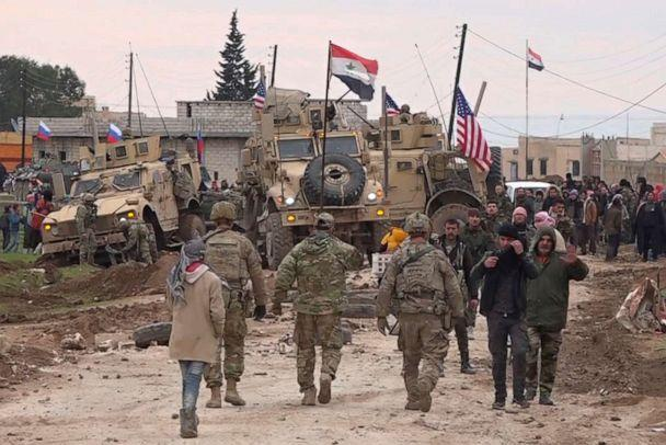 PHOTO: In this frame grab from video, Russians, Syrians and others gather next to an American military convoy stuck in the village of Khirbet Ammu, east of Qamishli city, Syria, Wednesday, Feb. 12, 2020. (AP)