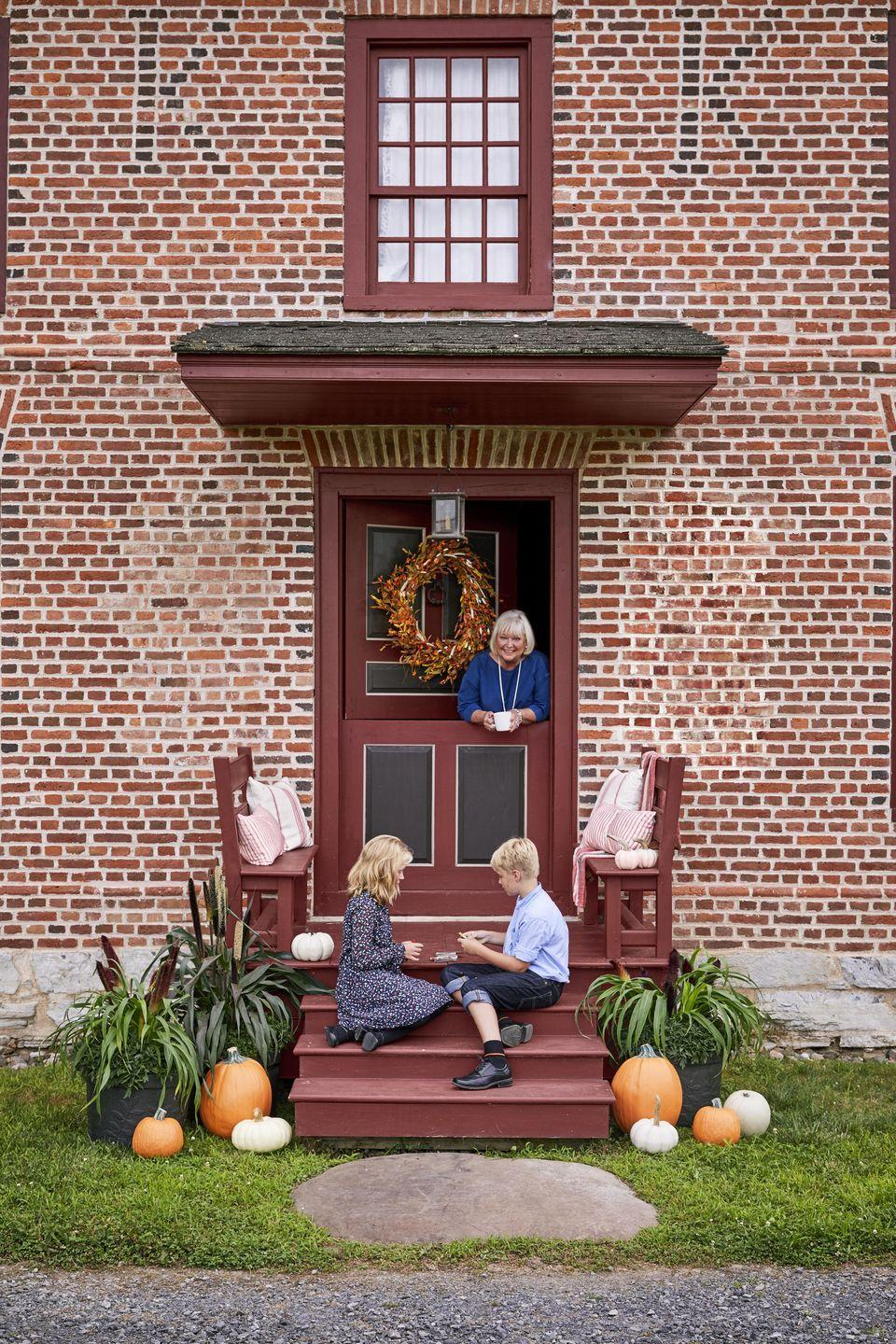 <p>This Dutch door and wee porch gets an oversize wreath made from a mixture of fall foliage. Pillows on built-in benches lend a soft touch.</p>