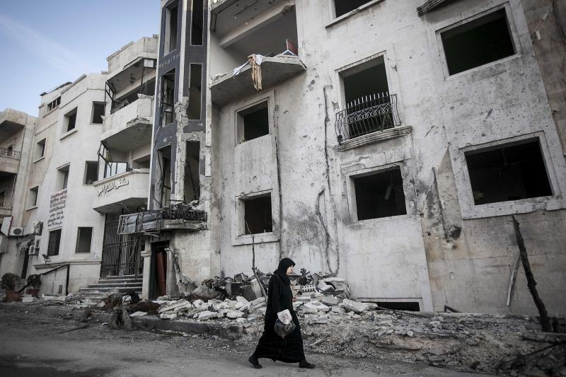 In this Saturday, Nov. 17, 2012 photo, a Syrian woman walks in front of a destroyed hospital where heavy clashes took place between rebel fighters and the Syrian army to seize control over the area, on the outskirts of Aleppo, Syria. There is a struggle for power among rebel factions in Syria with Islamists rejecting the country's new Western-backed opposition coalition and unilaterally declaring an Islamic state in the key battleground of Aleppo, though all of the groups are fighting to topple President Bashar Assad. (AP Photo/Narciso Contreras)