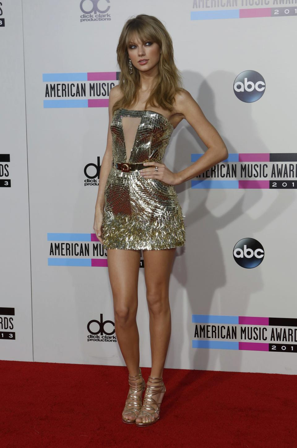 Taylor Swift was every inch the rock star tonight. Her thigh-high, fitted strapless metallic gold dress with the sheer front panel, paired with strappy gold sandals, loose hair and smoky eyes made her one of the best-dressed on the carpet. REUTERS/Mario Anzuoni (UNITED STATES - TAGS: ENTERTAINMENT)(AMA-ARRIVALS)