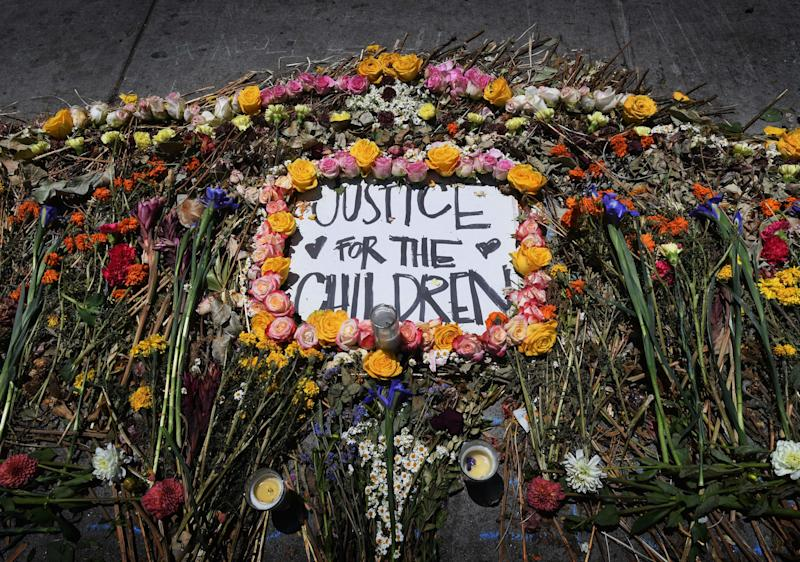 Flowers frame a message placed by protesters during march and rally against the separation of immigrant families June 30, 2018 outside the detention facility of the US Immigration and Customs Enforcement (ICE) in Los Angeles, California. - Thousands of demonstrators, baking in the heat and opposed to the US immigration policy, marched across the country Saturday, June 30, 2018 to protest the separation of families under President Donald Trump's hardline agenda. (Photo by Mark RALSTON / AFP) (Photo credit should read MARK RALSTON/AFP/Getty Images)