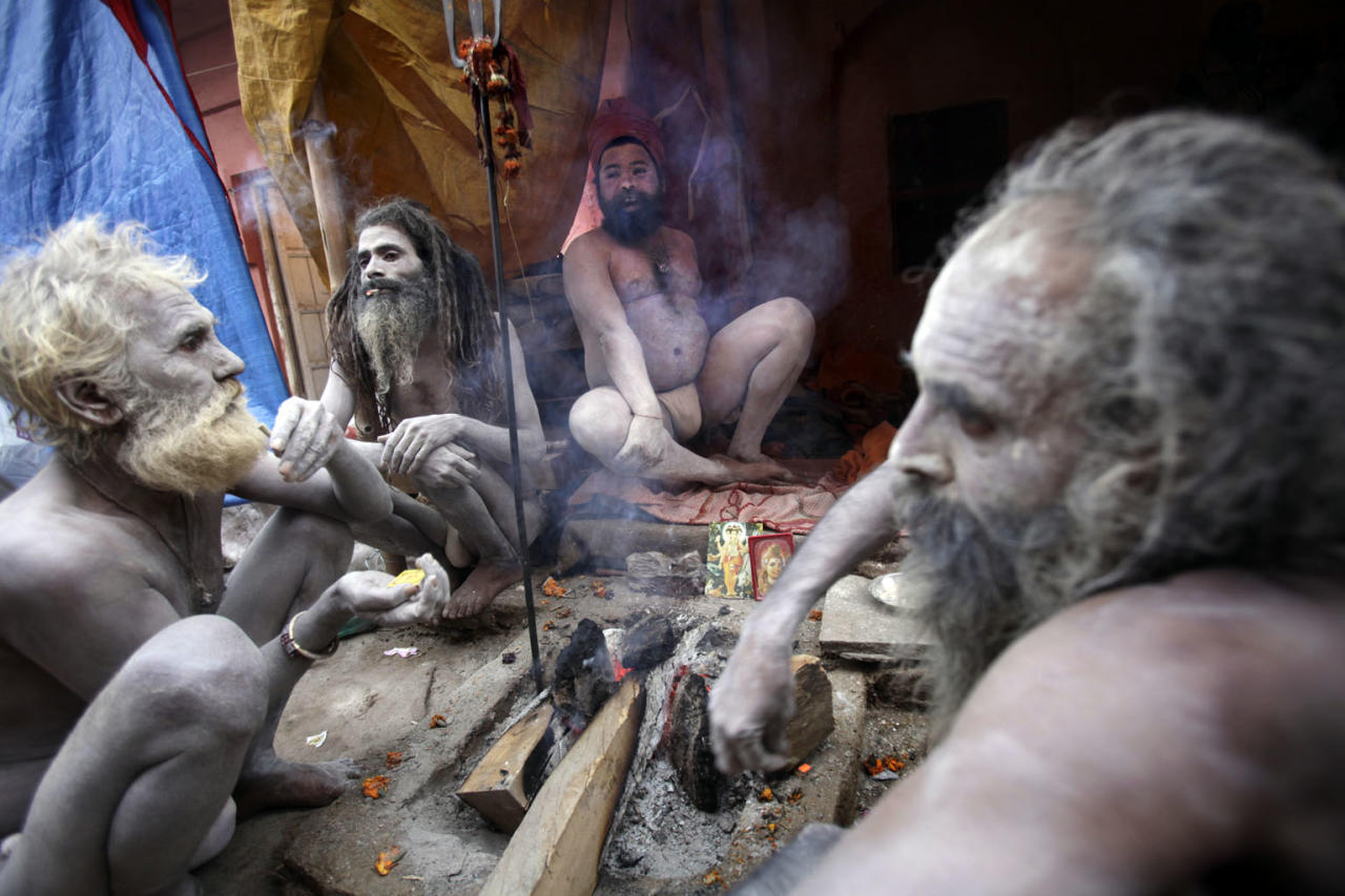 Sadhu (holy men) smoke during Kumbh Mela, the largest Hindu gathering in the world, February 12, 2010 in Haridwar, India. Hindus believe that bathing in the Ganges during the festival cleanses them of sin.  (Photo by Kuni Takahashi/Getty Images)
