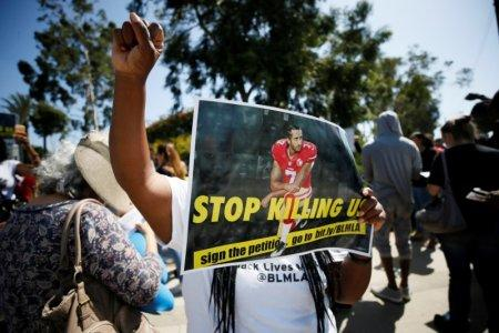 A protester demonstrates and holds a sign with Colin Kaepernick on it in support of NFL players who