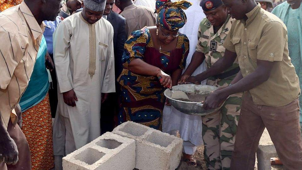 Ngozi Okonjo-Iweala using a trowel to scoop mortar from a pan