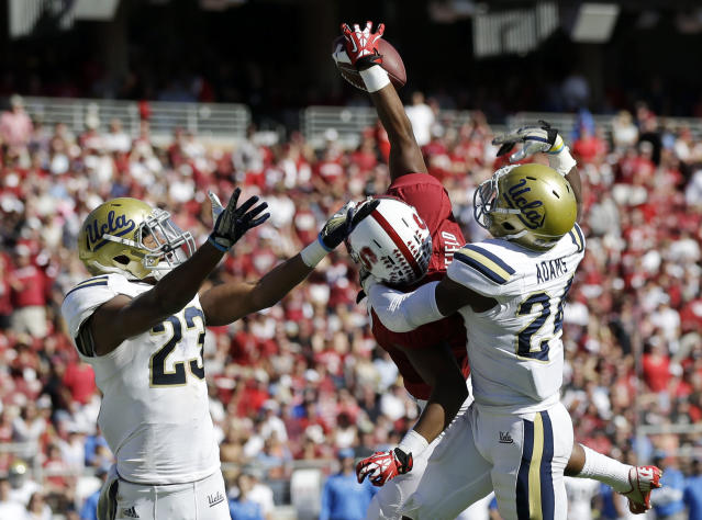 Stanford wide receiver Kodi Whitfield, center makes a one-handed touchdown catch next to UCLA cornerback Ishmael Adams, right, and cornerback Anthony Jefferson during the second half of an NCAA college football game on Saturday, Oct. 19, 2013, in Stanford, Calif. Stanford won 24-10. (AP Photo/Marcio Jose Sanchez)