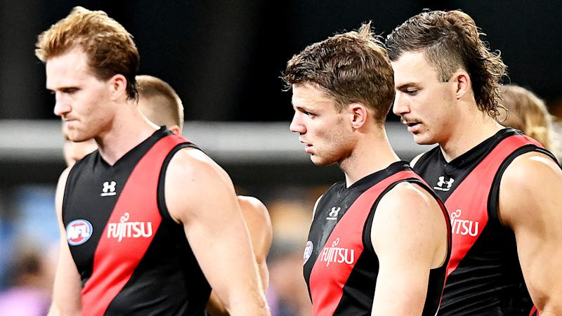 Essendon Bombers players are pictured walking off the field after their loss to Geelong.
