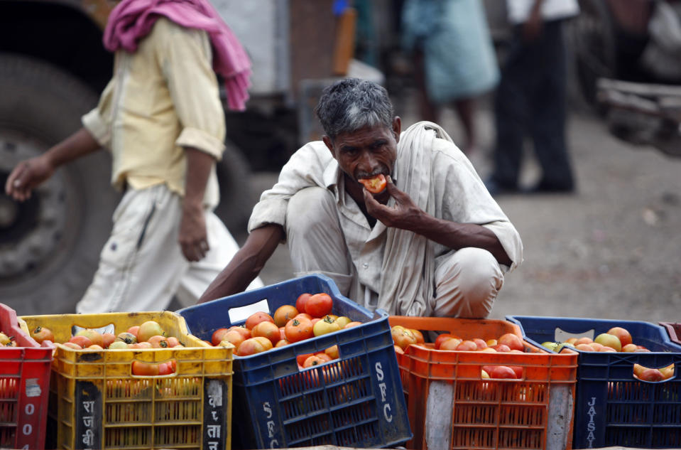 In this Aug. 3, 2011, file photo, a laborer eats a tomato at one of Asia's biggest wholesale markets, Azadpur mandi, in New Delhi, India. United Nations agencies are warning that more than 350 million people in the Asia-Pacific are going hungry as the coronavirus pandemic destroys jobs and pushes food prices higher. (AP Photo/Mustafa Quraishi, File)