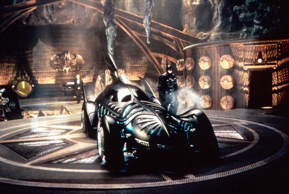 Batman (Val Kilmer) strikes a pose in the Batcave next to the Batmobile in <em>Batman Forever</em>. (Photo: Warner Bros./courtesy Everett Collection)