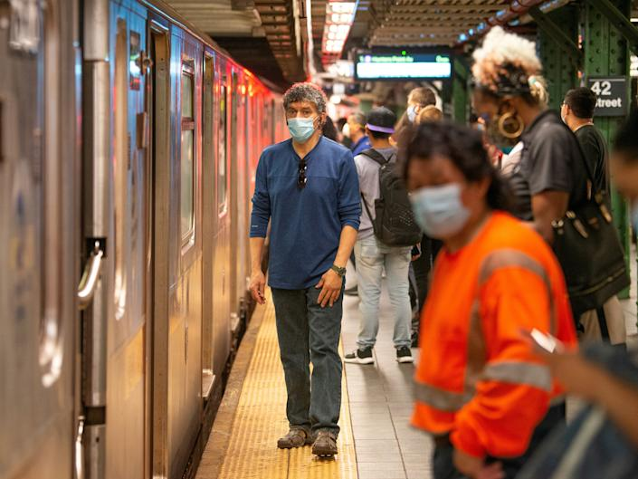 People wearing masks wait on a crowded subway platform on May 30, 2020, in New York City.