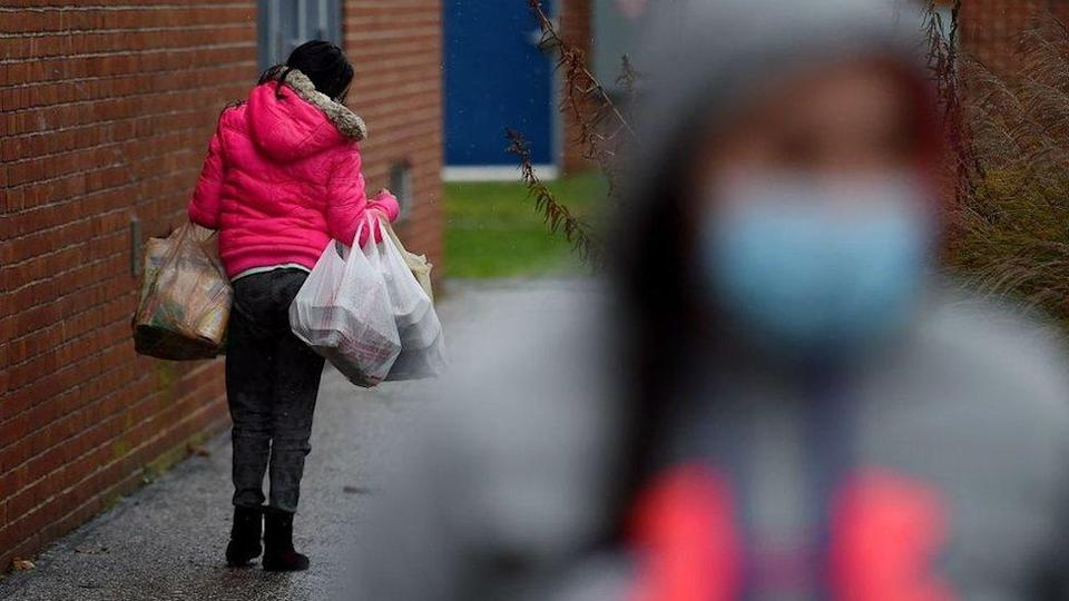 People carry food donated by volunteers from the Baltimore Hunger Project outside of Padonia International Elementary school