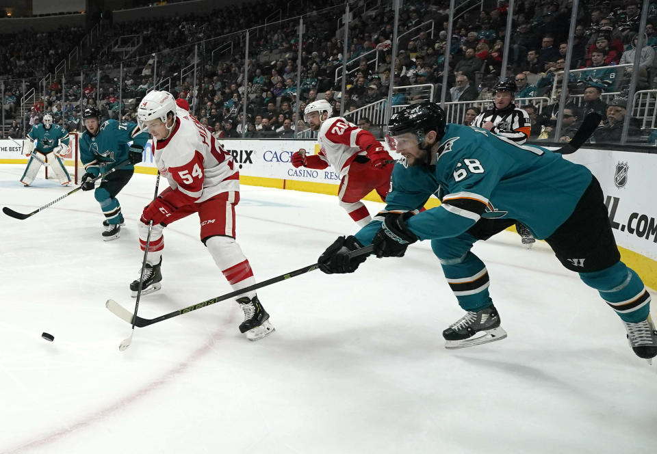 Detroit Red Wings left wing Matt Puempel (54) moves the puck past San Jose Sharks center Melker Karlsson (68) during the second period of an NHL hockey game Monday, March 25, 2019, in San Jose, Calif. (AP Photo/Tony Avelar)
