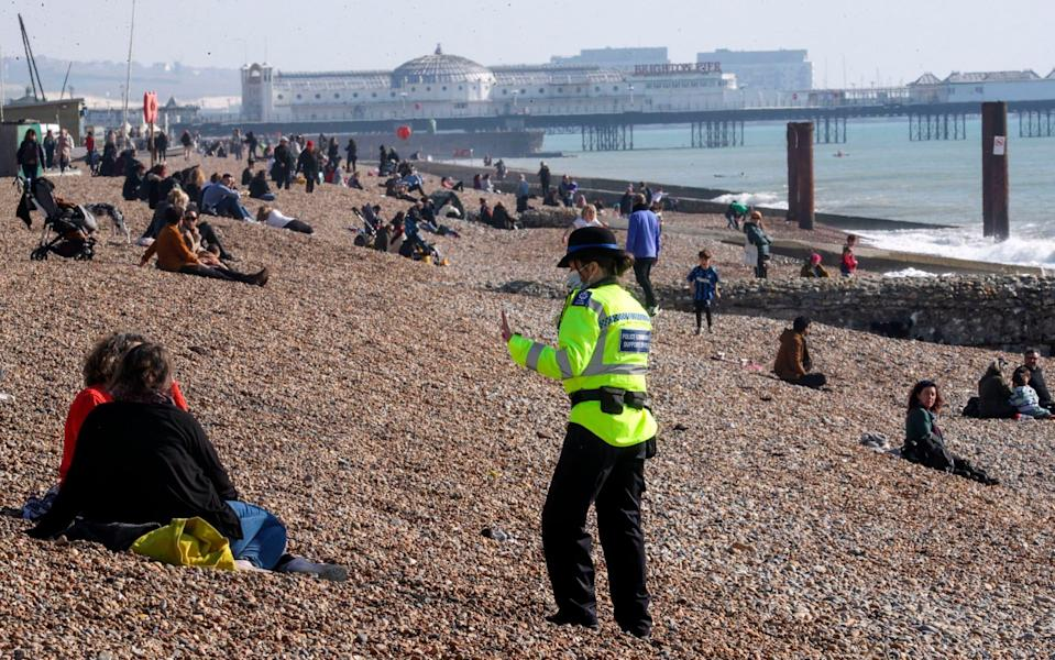 A community support officer speaks to people enjoying the sunshine on Brighton beach, in Sussex, on Sunday - Steve Parsons/PA