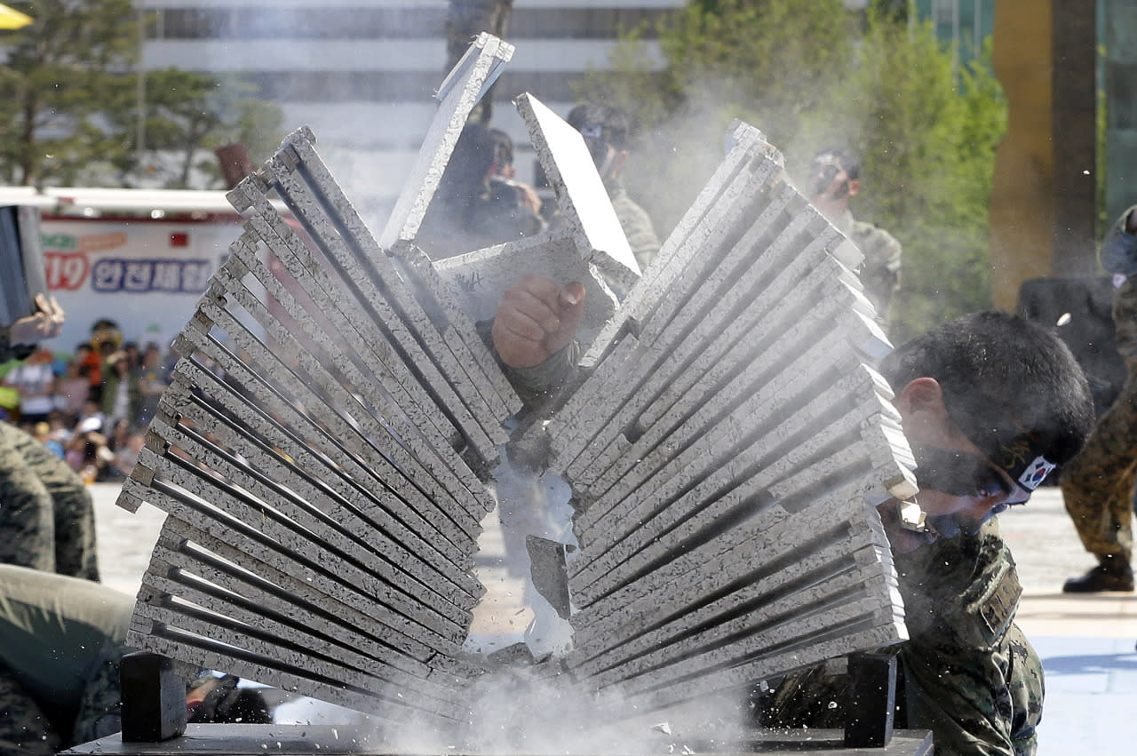 A soldier from the South Korean army special forces breaks stone plates with his hand during a martial arts demonstration for Children's Day at the War Memorial of Korea in Seoul, South Korea, May 5, 2016. In South Korea May 5 is celebrated as Children's Day, a national holiday. (Ahn Young-joon/AP)