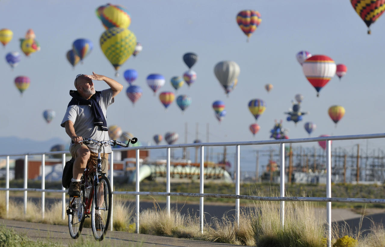 An unidentified bicyclist watches the mass ascension of hot air balloons while on a early morning bike ride along the North Diversion Channel path during the first morning of the Albuquerque International Balloon Fiesta, Saturday, Oct. 2, 2010, in Albuquerque, N.M.