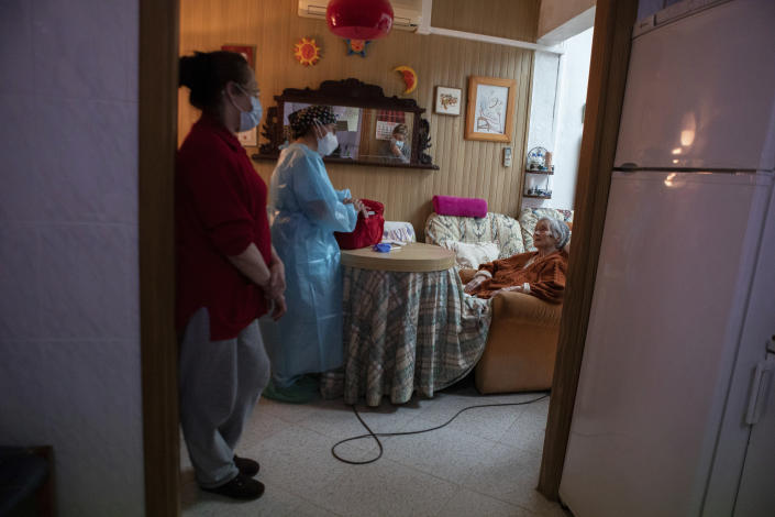 Nurse Pilar Rodríguez speaks with her patient Antonia Crespi Gomila after administering the vaccine against COVID-19 at her home in the town of Sa Pobla on the Spanish Balearic Island of Mallorca, Spain, Friday, April 30, 2021. (AP Photo/Francisco Ubilla)