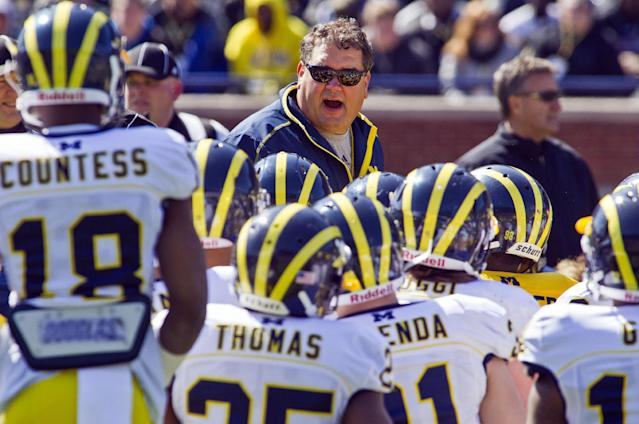 Michigan head coach Brady Hoke, center top, huddles with his players during the football team's NCAA college spring football game, Saturday, April 5, 2014, in Ann Arbor, Mich. (AP Photo/Tony Ding)