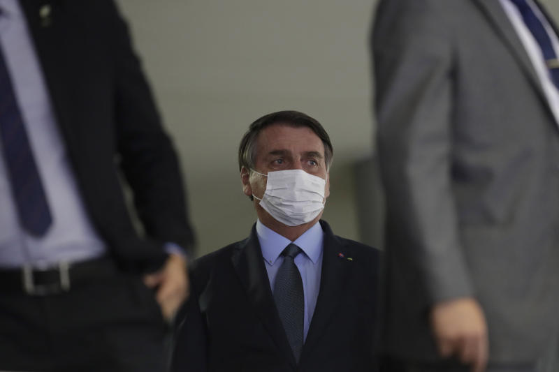 Brazil's President Jair Bolsonaro, wearing a mask to curb the spread of COVID-19, arrives to attend a ceremony at the Planalto Presidential Palace, in Brasilia, Brazil, Wednesday, Sept. 16, 2020. After almost four months overseeing the COVID-19 response as interim health minister, Gen. Eduardo Pazuello will finally be made a full minister. (AP Photo/Eraldo Peres)