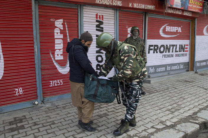 An Indian paramilitary soldier checks the bag of a Kashmiri man during a strike in Srinagar, Indian controlled Kashmir, Sunday, Feb. 3, 2019. India's prime minster is in disputed Kashmir for a daylong visit Sunday to review development work as separatists fighting Indian rule called for a shutdown in the Himalayan region. (AP Photo/Dar Yasin)