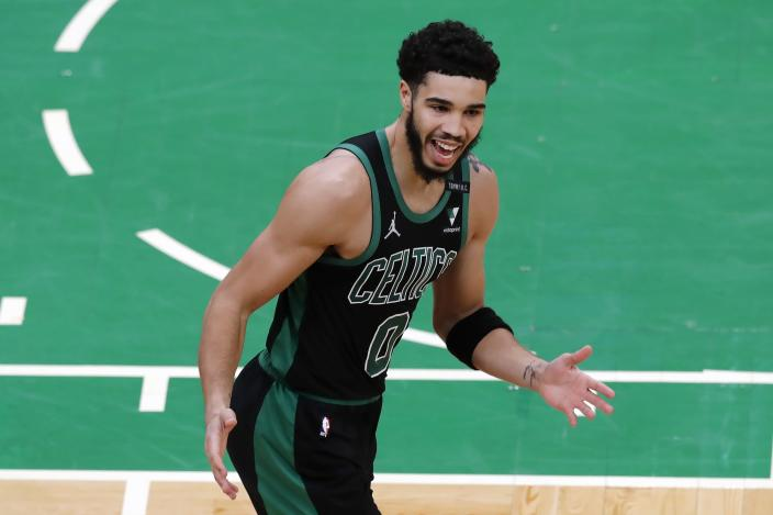 Boston Celtics' Jayson Tatum asks for a call after dunking against Charlotte Hornets' Miles Bridges during the first half of an NBA basketball game Sunday, April 4, 2021, in Boston. (AP Photo/Michael Dwyer)