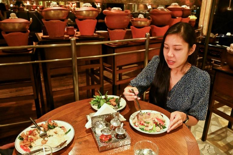 Kindergarten teacher Diane Piroon tries a vegetarian version of yam woon sen, a spicy glass noodle salad made with a meat substitute, at a restaurant in Bangkok