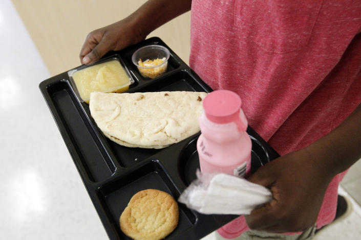 A student at Eastside Elementary School in Clinton, Miss., carries out a noon meal consisting of a flat bread roast beef sandwich, apple sauce, strawberry milk and a cookie, Wednesday, Sept. 12, 2012. The leaner, greener school lunches served under new federal standards are getting mixed grades from students. (AP Photo/Rogelio V. Solis)