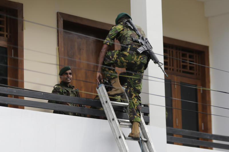A Sri Lankan police commando enters a house suspected to be a hideout of militants following a shoot out in Colombo, Sri Lanka, Sunday, April 21, 2019. More than hundred were killed and hundreds more hospitalized with injuries from eight blasts that rocked churches and hotels in and just outside of Sri Lanka's capital on Easter Sunday, officials said, the worst violence to hit the South Asian country since its civil war ended a decade ago. (AP Photo/Eranga Jayawardena)