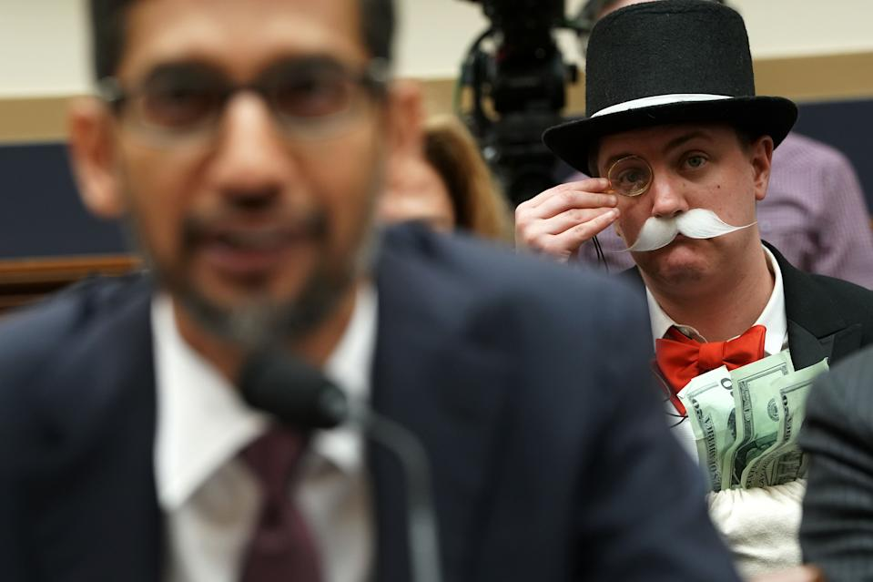 "WASHINGTON, DC - DECEMBER 11: Ian Madrigal (R) dresses as Mr. Monopoly as Google CEO Sundar Pichai (L) testifies before the House Judiciary Committee at the Rayburn House Office Building on December 11, 2018 in Washington, DC. The committee held a hearing on 'Transparency & Accountability: Examining Google and its Data Collection, Use and Filtering Practices.""  (Photo by Alex Wong/Getty Images)"