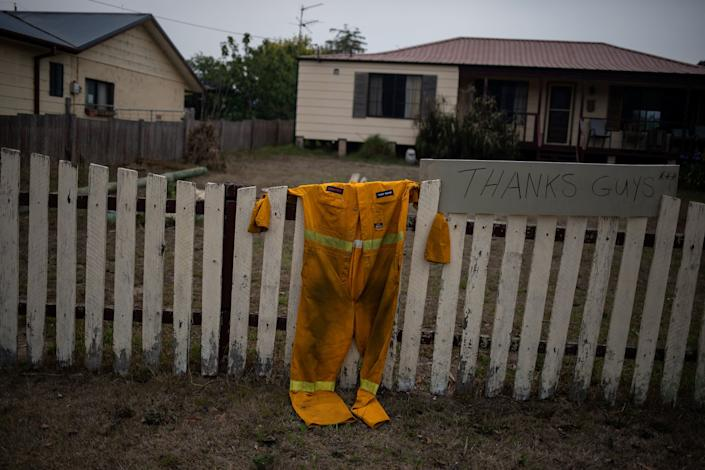 "A firefighter's suit hangs on a fence next to a ""Thanks guys"" sign in Cobargo, New South Wales, Australia, on Jan. 12. (Photo: Alkis Konstantinidis / Reuters)"