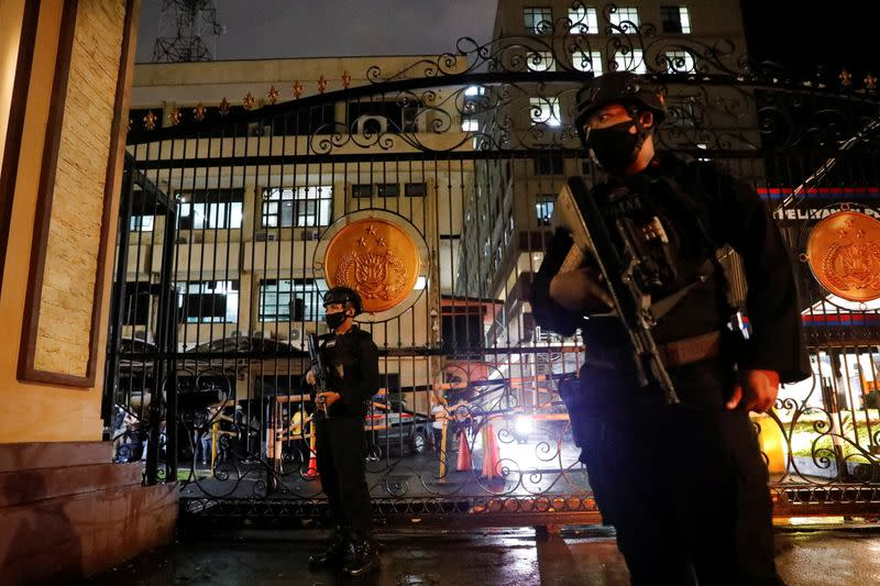 Armed police officers stand guard outside the gate of national police headquarters, in Jakarta