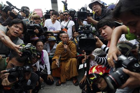 Thai Buddhist monk Luang Pu Buddha Issara is surrounded by his supporters and reporters at a police compound housing a government security group, north of Bangkok