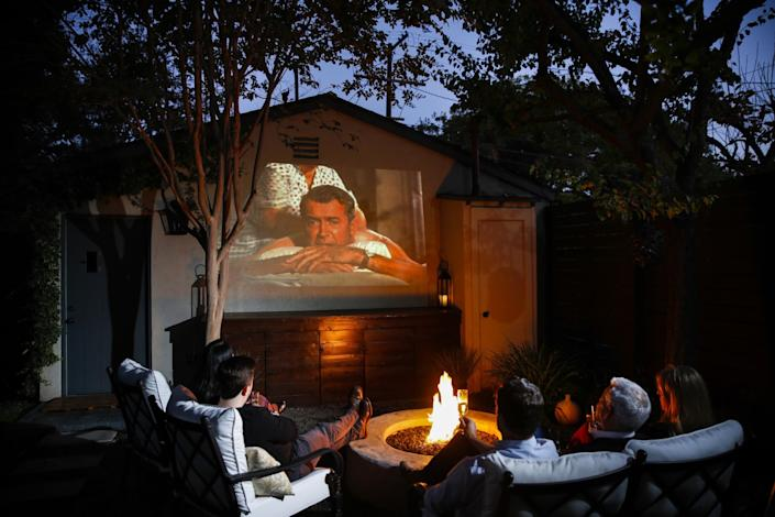 "Chad Rothman and Michael Moore enjoy movie night in the backyard of their home in the Brookside neighborhood, just south of Hancock Park. <span class=""copyright"">(Jay L. Clendenin / Los Angeles Times)</span>"