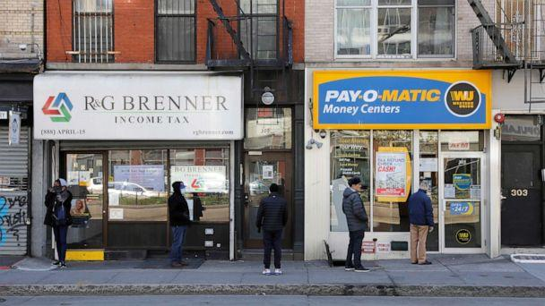 PHOTO:People queue to enter Payomatic, a business that offers check cashing, as unemployment claim figures were released, during the coronavirus disease (COVID-19) outbreak in Manhattan, New York City, April 2, 2020. (Andrew Kelly/Reuters)
