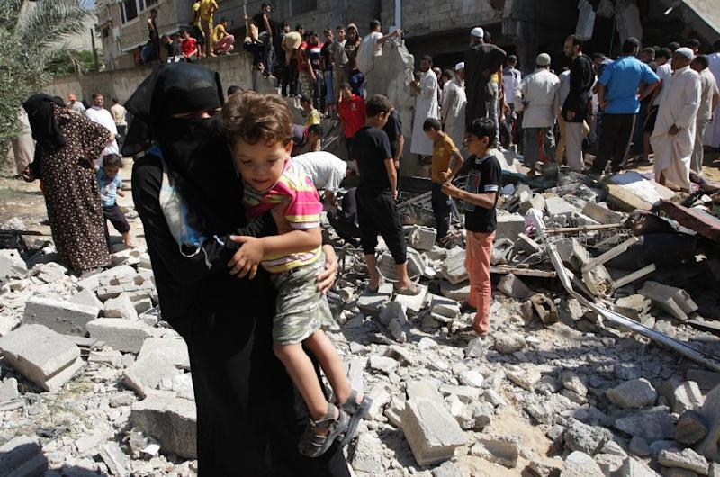 A Palestinian woman carrying a child makes her way through debris as people inspect the remains of a house belonging to a member of the Islamist Hamas movement following an Israeli air strike on July 8, 2014 in the Gaza strip town of Khan Yunis (AFP Photo/Said Khatib)