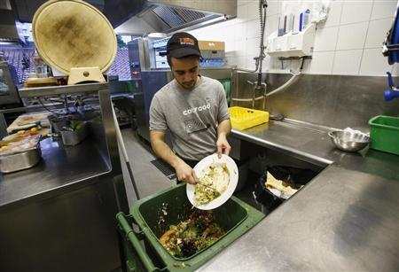 A cook throws away leftovers in the 'Auf da Muehle' restaurant in Soell