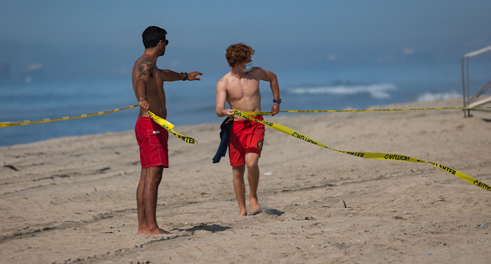 Two lifeguards roping off Huntington Beach using police tape.
