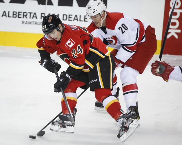 Carolina Hurricanes' Riley Nash, right, tries to steal the puck from Calgary Flames' Jiri Hudler, from the Czech Republic, during first period NHL hockey action in Calgary, Alberta, Thursday, Dec. 12, 2013. (AP Photo/The Canadian Press, Jeff McIntosh)