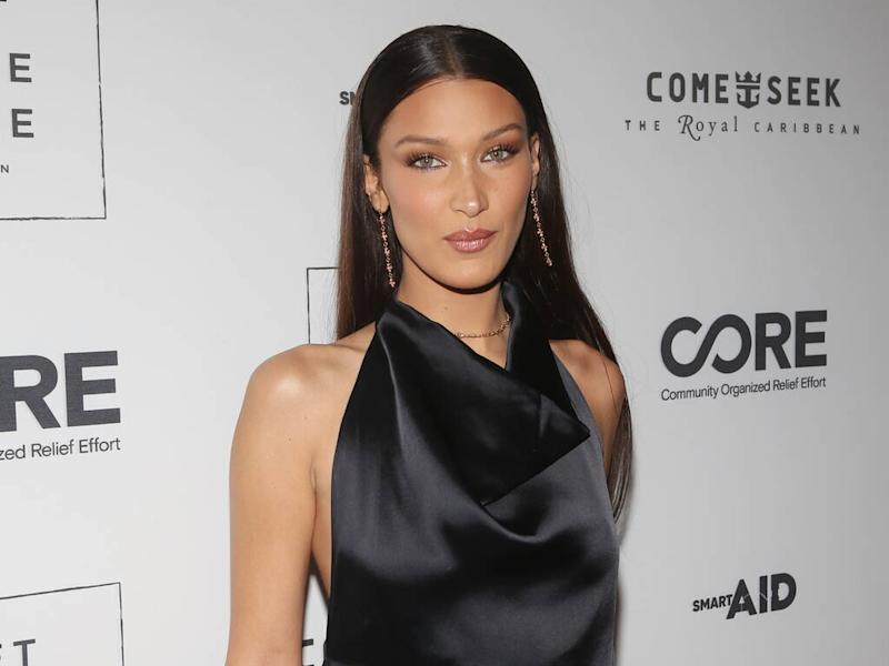 Bella Hadid urges fans to practice social distancing with topless snap