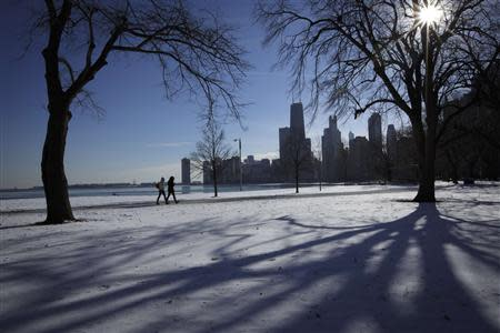 Two women walk along the shore of Lake Michigan in Chicago where temperatures have dropped well below freezing, December 12, 2013. REUTERS/John Gress