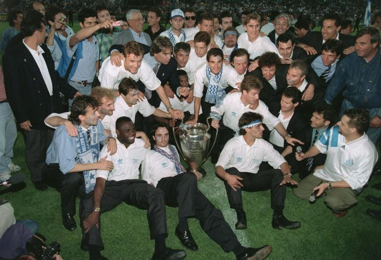 Bernard Tapie, in shirt and tie behind the trophy, poses with the Marseille players who won the 1993 European Cup (AFP/BORIS HORVAT)