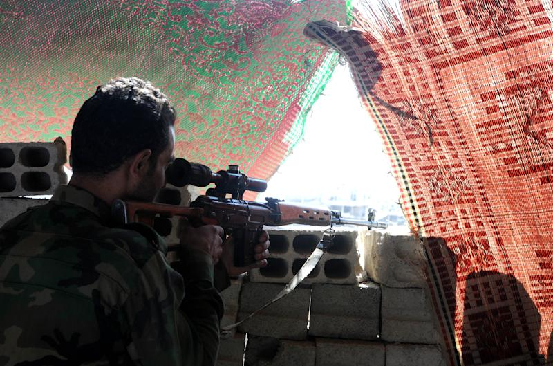 A Syrian soldier aims a sniper rifle during clashes in Jobar, on the outskirts of Damascus, on October 18, 2014 (AFP Photo/)