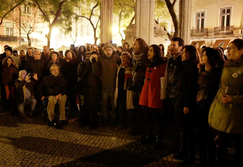 """In this photo taken Feb. 23, 2013, people gather at Lisbon's Largo do Carmo square to sing """"Grandola, Vila Morena"""" (Grandola, Dusky Town) to mark the 26th anniversary of the death of it's author, Zeca Afonso. A Portuguese revolutionary song from 40 years ago is haunting the bailed-out country's government. Anti-austerity protesters are hounding senior officials by loudly singing at public events a celebrated tune from the 1974 Carnation Revolution. They have managed to silence some of their targets, including the prime minister when he was trying to give a speech in Parliament. (AP Photo/Armando Franca)"""