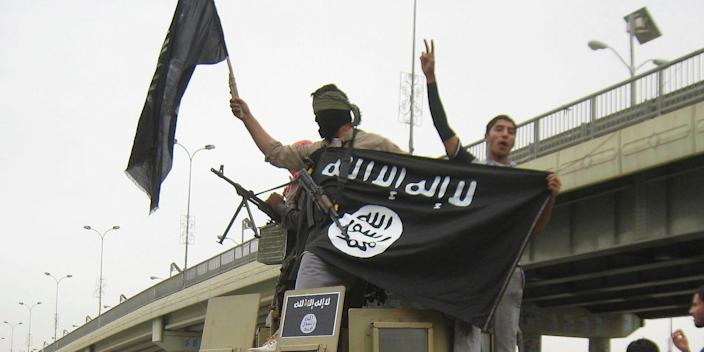 Islamic State group militants hold up their flag as they patrol in a commandeered Iraqi military vehicle in Fallujah, Iraq in 2014.